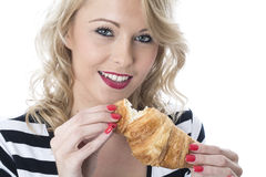 Young Woman Eating a Breakfast Croissant Royalty Free Stock Images