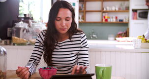 Young Woman Eating Breakfast Whilst Using Digital Tablet stock footage