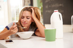 Young Woman Eating Breakfast Whilst Using Mobile Phone Royalty Free Stock Photography
