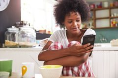 Young Woman Eating Breakfast Whilst Using Mobile Phone Royalty Free Stock Photos
