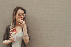 Young woman eating bubble waffle with fruits, chocolate and marshmallow, with copy space Stock Photos