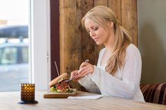 Young Woman Eating Burger At Restaurant Stock Photo