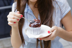 Young woman eating cake in outdoor cafe. Closeup Stock Photography