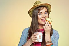 Young woman eating cake with tea or coffee. Stock Photos