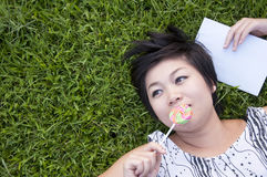 Young woman eating a candy in field Royalty Free Stock Image
