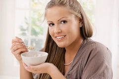 Young woman eating ceral. Beautiful young woman eating breakfast cereal. Selective focus on face Royalty Free Stock Photo
