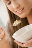 Young woman eating cereal Royalty Free Stock Images