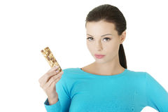 Young woman eating Cereal candy bar. Isolated on white Royalty Free Stock Photo