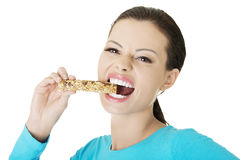 Young woman eating Cereal candy bar. Isolated on white Stock Photos