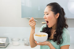 Young woman eating cereals in kitchen Stock Images