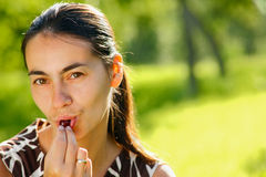 Young woman eating a cherry. A young woman eating a handful of cherries outdoors Royalty Free Stock Image