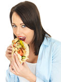 Young Woman Eating Chicken Kebab with Salad Stock Image