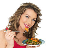 Young Woman Eating a Chicken Tikka and Rice Salad Royalty Free Stock Image