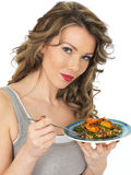 Young Woman Eating Chicken Tikka with Wild Rice Salad Stock Photos