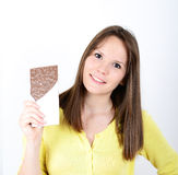 Young woman eating chocolate bar against white background Royalty Free Stock Images