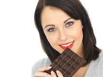 Young Woman Eating a Chocolate Bar. Attractive Young Woman Eating a Chocolate Bar Royalty Free Stock Image