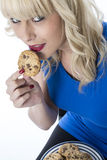 Young Woman Eating a Chocolate Chip Cookie Biscuit Royalty Free Stock Images