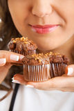 Young woman eating chocolate muffin Stock Photos