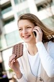 Young woman eating chocolate on the phone Stock Photo