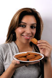 Young woman eating cookies. A studio portrait of a young Asian girl, holding a plate of cookies, about to eat one of them royalty free stock photography