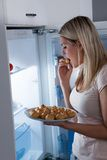 Young woman eating cookies Royalty Free Stock Photos