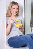 Young woman eating corn flakes at home Stock Photography