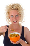 Young woman eating cornflakes. Young blonde woman eating cornflakes from a bowl Royalty Free Stock Image