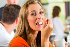 Young woman eating cream in cafe Stock Photo