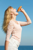 Young woman eating croissant food outdoor. Stock Photos