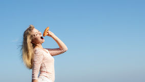 Young woman eating croissant food outdoor. Royalty Free Stock Photos
