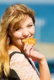 Young woman eating croissant food outdoor. Royalty Free Stock Photography
