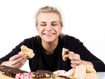 Young woman eating cupcakes with pleasure after a diet.