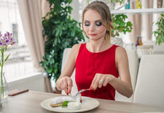 Young woman eating delicious strudel at restaurant. Lady in red Royalty Free Stock Images