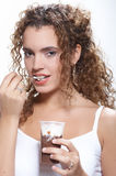Young woman eating dessert. Head and shoulders studio shot of a multiracial young woman eating from a dessert cup Royalty Free Stock Images