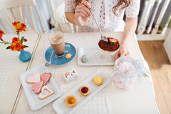 Young woman eating dessert and drinking latte at the table Royalty Free Stock Image