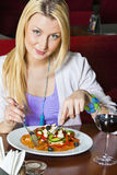 Young Woman Eating Dinner Stock Images
