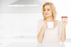 Young woman eating donut with morning coffee Stock Photo
