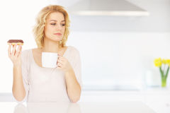 Young woman eating donut with morning coffee Royalty Free Stock Image