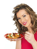 Young Woman Eating a Feta Cheese and Tommato Pasta Salad. A DSLR royalty free image of an attractive young woman with dark blonde hair, holding a plate full of Royalty Free Stock Image