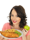Young Woman Eating Fish and Chips with Mushy Peas Stock Photo