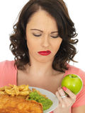 Young Woman Eating Fish and Chips with Mushy Peas Royalty Free Stock Photo