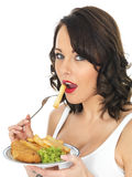 Young Woman Eating Fish and Chips and Mushy Peas Royalty Free Stock Images