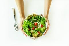 Young woman eating fresh organic vegetarian salad stock photography