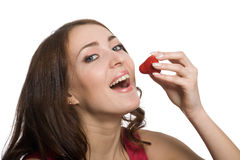 Young woman eating a fresh red strawberry Royalty Free Stock Photos