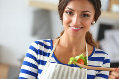 Young woman eating fresh salad in modern kitchen Stock Photography