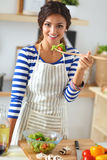 Young woman eating fresh salad in modern kitchen Royalty Free Stock Photos