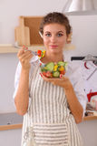 Young woman eating fresh salad in modern kitchen Royalty Free Stock Images