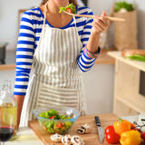 Young woman eating fresh salad in modern kitchen Stock Photo