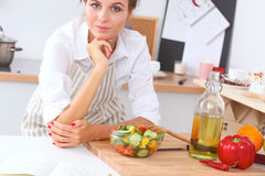 Young woman eating fresh salad in modern kitchen Royalty Free Stock Photography