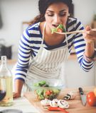 Young woman eating fresh salad in modern kitchen stock images
